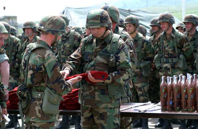 The Republic of Georgia Army Commanding Officer from the 16th Mountain Battalion presents a red beret to one of his Soldiers, during a Certification Ceremony, held at the Krtsanisi Training Area, Rock City, Georgia. The ceremony marks the completion of the third tactical training phase for Soldiers participating in the program. GETEP is a phased training initiative that enhances operational capabilities of select Georgian units to increase security of Georgia's borders and promote stability within the region