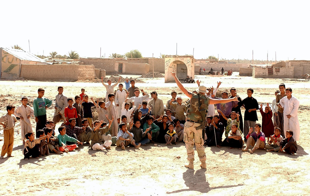 US Navy (USN) Utilitiesman Third Class (UT3) Justin Walker, assigned to Naval Mobile Construction Battalion Seven (NMCB-7) entertains a group of Iraqi children, while members of his unit complete repair work inside an local school near An Nasariyah, Iraq, during Operation IRAQI FREEDOM