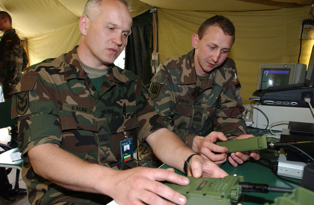 Lithuanian Army Transmission Technicians, MASTER Sergeant (MSGT) Kestutes Balke (left) and Sergeant (SGT) Arturas Hiksa, test high frequency radio links at Lager Aulenbach, Germany, during Exercise COMBINED ENDEAVOR 2003. The Exercise is a Partnership for Peace (PfP) exercise hosted by Germany, and is the largest information and communications systems exercise in the world which focuses primarily on Command, Control, Communications, and Computers (C4) interoperability testing and documentation