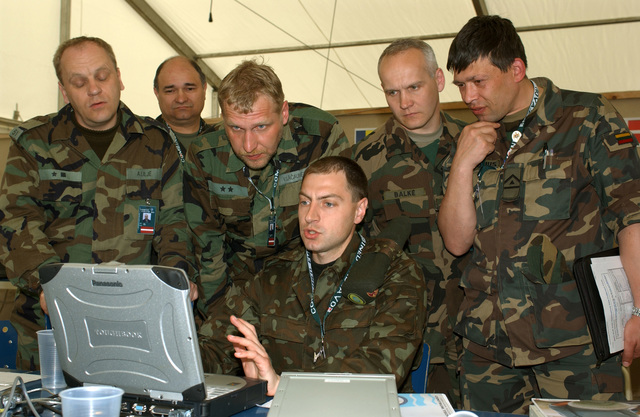 Ukraine Army Single Channel Radio Technician Captain (CPT) Dmytro Lyulin (seated center), uses a Panasonic TOUCHBOOK computer to test a radio automatic link establishment (ALE) for member of the Ukraine and Lithuanian Army contingent, during a workshop at Lager Aulenbach, Germany, during Exercise COMBINED ENDEAVOR 2003. The Exercise is a Partnership for Peace (PfP) exercise hosted by Germany, and is the largest information and communications systems exercise in the world which focuses primarily on Command, Control, Communications, and Computers (C4) interoperability testing and documentation