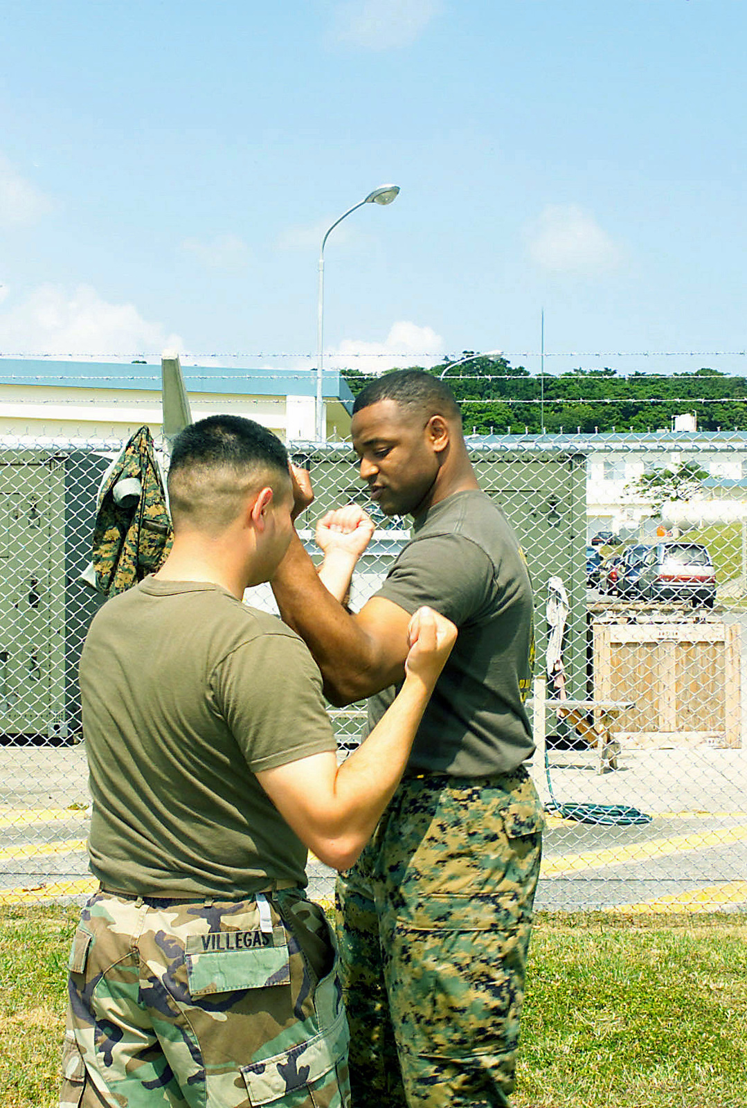 US Marine Corps (USMC) Corporal (CPL) Joe Villegas (left), a Videographer assigned to the Combat Visual Information Center (CVIC), and USMC Sergeant (SGT) Elvis Raines, a Graphic Artist assigned to the CVIC, demonstrate body-hardening exercises during a tan belt instructions course, part of the Marine Corps Martial Arts Program (MCMAP) at Camp Foster, Okinawa, Japan