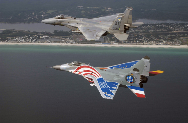 "A dramatically painted Russian designed MiG-29 fighter flown by German Luftwaffer pilot Lieutenant Colonel (LCOL) Tom Hahn, Squadron Commander (SC) of Germany's (DEV) 73rd Fighter Wing (FW) or ""Steinhoff,"" stays in formation with a US Air Force (USAF) F-15C Eagle piloted by Major (MAJ) Greg Thomas, from the 28th Test Squadron (TS), Nellis Air Force Base (AFB), Nevada, over the Gulf of Mexico during a joint training exercise"