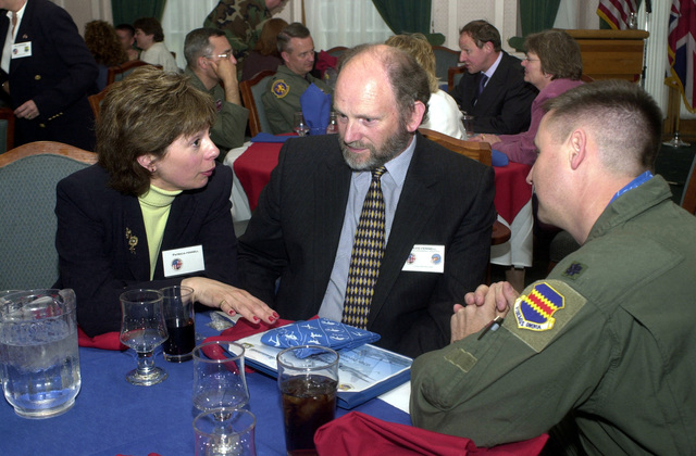 Patricia and David Fennell, from the Immigration Office at Royal Air Force (RAF) Mildenhall, United Kingdom (UK), talk with US Air Force (USAF) Lieutenant Colonel (COL) Steven Ling, 95th Reconnaissance Squadron, during the Honorary Commander's Induction Ceremony. This unique program allows military and civilian organizations to foster positive community relations