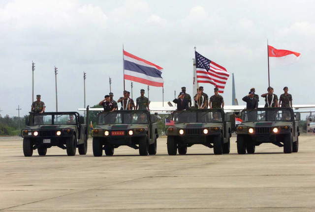 A motorcade of M998 High-Mobility Multipurpose Wheeled Vehicles (HMMWV) carrying Commanders from a Combined Task Force (CTF) representing Thailand, Singapore, and the US, moves down the flight line during the opening ceremony for Exercise COBRA GOLD 2003, held at Utapao National Airport, Thailand