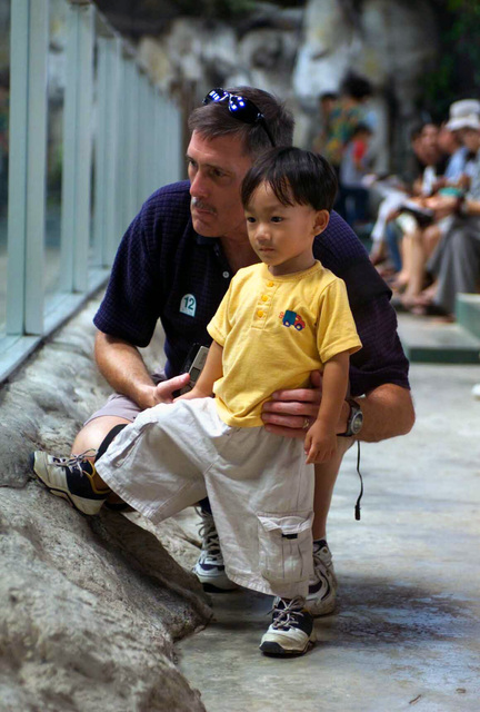Gary Weeden, US Navy (USN), Chaplain from Washington D.C. looks into a glass cage of alligators with an orphan from the El Shaddai Orphanage in Thailand at the Sriracha Tiger Zoo, during a visit by US Marine Corps (USMC) personnel and USN Sailors from Marine units in Sameson, as part of a regional community relations effort in support of Exercise COBRA GOLD 2003