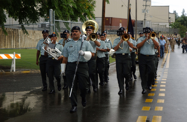 The Puerto Rico Army National Guard Band marches and performs in the rain during the Armed Forces Day Parade Celebration, held at Fort Buchanan, Puerto Rico