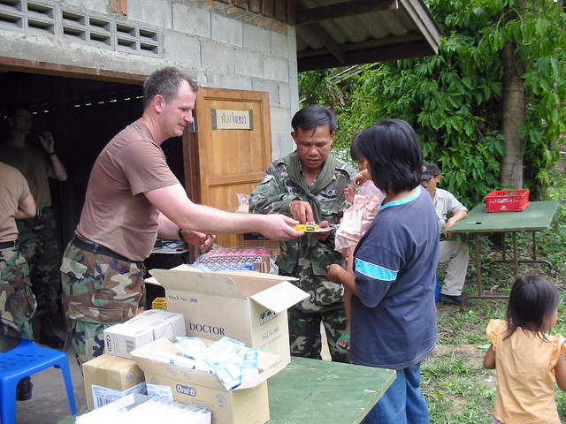 A Royal Thai Army soldier helps a US Army (USA) soldier assigned to the 2nd Battalion, 1ST Special Forces Group (SFG) Airborne, with handing out books and cereal to local Thai villagers, during the Medical Community Assistance Program at Ban Dong, Thailand, during Exercise COBRA GOLD 2003
