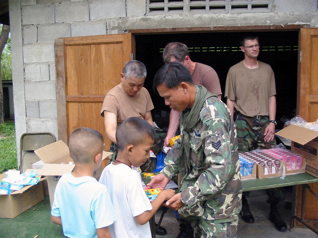 A Royal Thai Army soldier helps US Army (USA) Civil Military Affairs personnel assigned to the 426th Civil Affairs Battalion, with handing out books and cereal to children, during the Medical Community Assistance Program at Ban Dong, Thailand, during Exercise COBRA GOLD 2003