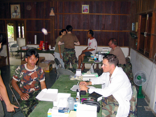 A US Army (USA) Medical Doctor assigned to 2nd Battalion, 1ST Special Forces Group (SFG) Airborne, prepares to examine a local Thai man during the Medical Community Assistance Program (MEDCAP) at Ban Dong, Thailand, during Exercise COBRA GOLD 2003