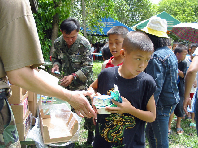 Local Thai children received books and cereal US Army (USA) soldier assigned to the 2nd Battalion, 1ST Special Forces Group (SFG) Airborne, during the Medical Community Assistance Program at Ban Dong, Thailand, during Exercise COBRA GOLD 2003
