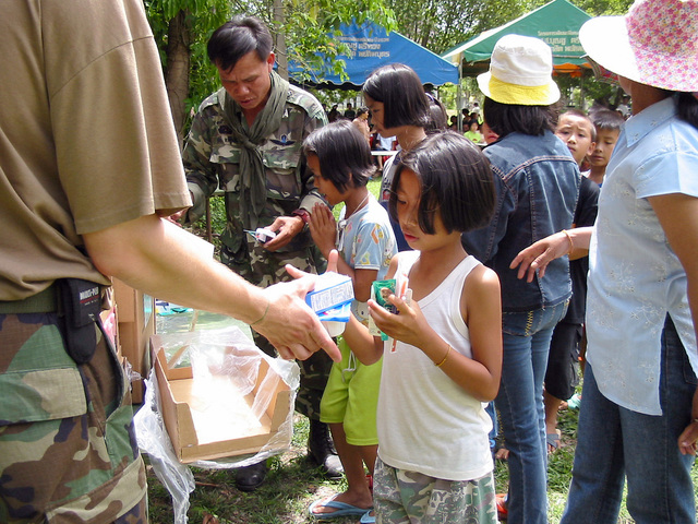 Royal Thai Army soldiers and US Army (USA) soldiers hand out cereal, and care packages to local Thai villagers, during the Medical Community Assistance Program at Ban Dong, Thailand, during Exercise COBRA GOLD 2003