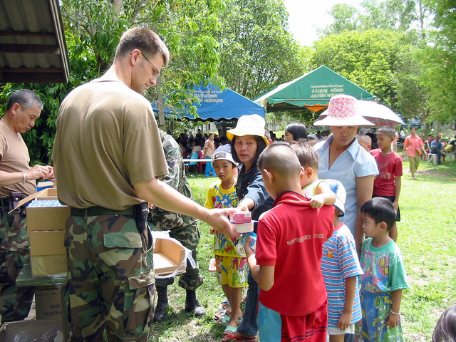 US Army (USA) soldier assigned to the 2nd Battalion, 1ST Special Forces Group (SFG) Airborne, hand out books and cereal to local Thai villagers, during the Medical Community Assistance Program at Ban Dong, Thailand, during Exercise COBRA GOLD 2003