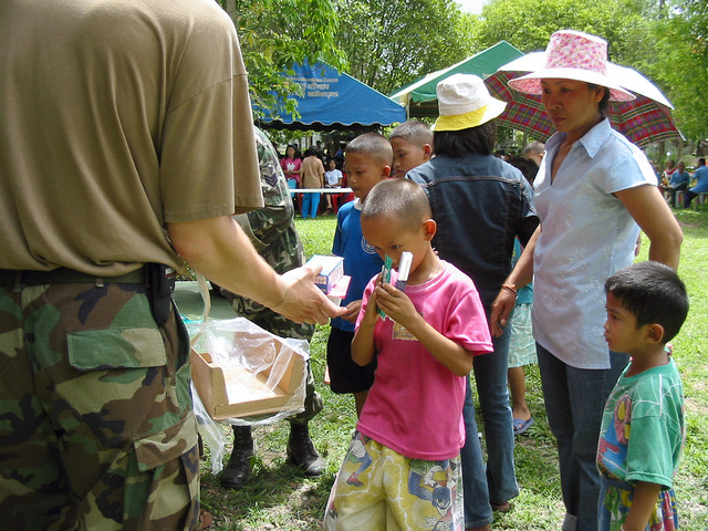 US Army (USA) soldiers hand out books, cereal, and care packages to local Thai villagers, during the Medical Community Assistance Program at Ban Dong, Thailand, during Exercise COBRA GOLD 2003