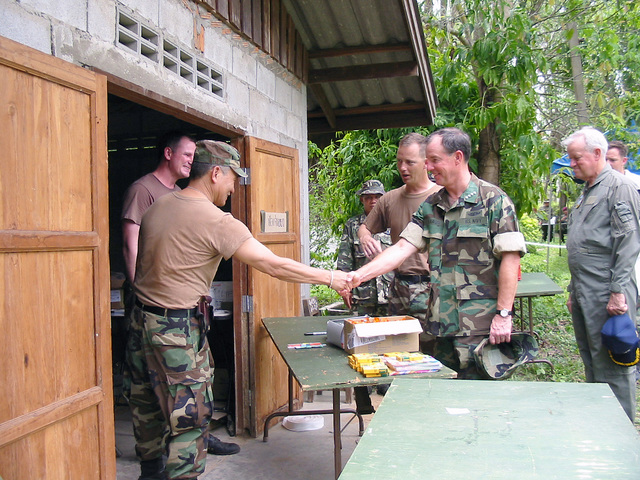 US Navy (USN) Admiral (ADM) Thomas Fargo (right), Commander, US Pacific Command, shakes hands with US Army (USA) CHIEF Warrant Officer (CWO3) Ron Owan, 426th Civil Affairs Battalion, while visiting the Medical Community Assistance Program (MEDCAP) at Ban Dong, Thailand, during Exercise COBRA GOLD 2003
