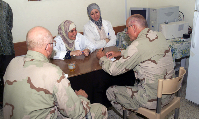Captain (CPT) John H. Nedeau, 3rd Battalion, 23rd Marines Battalion Surgeon and Commander John M. Dawson, Assistant Battalion Surgeon, discuss the medical needs of Al Numaniyah's local health clinic with Dr. Wedad and her head nurse in Iraq, during Operation IRAQI FREEDOM