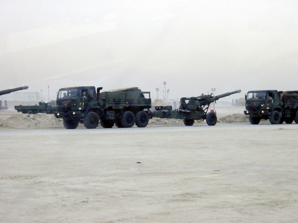 Elements of the US Army (USA) Division Artillery Brigade (DIVARTY), Ground Assault Convoy (GAC) consisting of M1083 Medium Tactical Vehicle (MTV) (6X6) 5-ton standard cargo trucks, towing M198 155mm towed howitzers, stopped along a roadside in Iraq, during Operation IRAQI FREEDOM