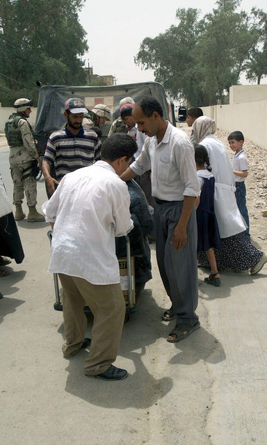 Iraqi medical staff at Al Numaniyah's local health clinic, unload medical supplies delivered by 3rd Battalion, 23rd Marine medical detachment, during Operation IRAQI FREEDOM