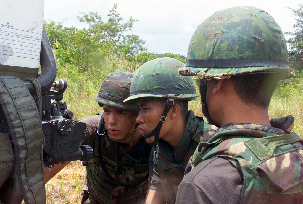 US Marine Corps (USMC) Lance Corporal (LCPL) Michael Stephens (left) shows two Royal Thai Marines how to check and verify coordinates for the firing position of the M198 155mm Howitzer, during a dry fire exercise at Gun Position 10, Pong Nam Ran, Thailand, during Exercise COBRA GOLD 2003