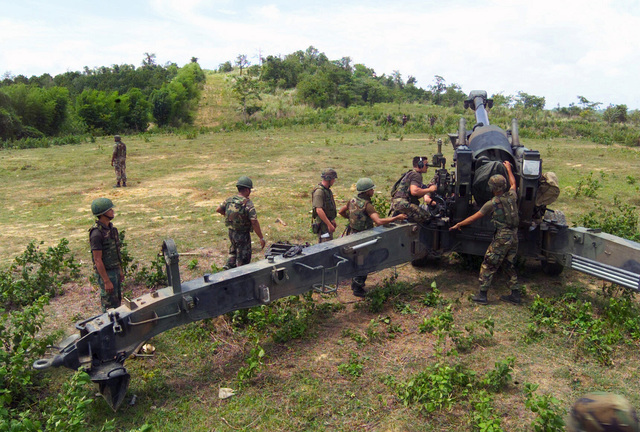 US Marine Corps (USMC) Marine assigned to S/Battery, 5th Battalion, 10th Marines, and Royal Thai Marines set up a M198 155mm Howitzer emplacement during a dry fire exercise at Gun Position 10, Pong Nam Ran, Thailand, during Exercise COBRA GOLD 2003
