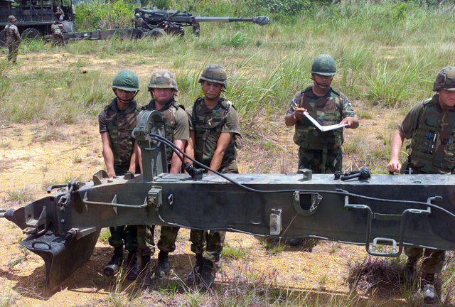 US Marine Corps (USMC) Marines assigned to S/Battery, 5th Battalion, 10th Marines, and Royal Thai Marines set up a M198 155mm Howitzer emplacement during a dry fire exercise at Gun Position 10, Pong Nam Ran, Thailand, during Exercise COBRA GOLD 2003