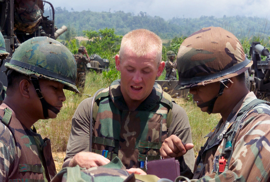 US Marine Corps (USMC) Sergeant (SGT) Jason Weatherby (center), S/Battery, 5th Battalion, 10th Marines, checks bearing with a Thai Royal Marines before firing M198 155mm Howitzers during a dry fire exercise at Gun Position 10, Pong Nam Ran, Thailand, during Exercise COBRA GOLD 2003