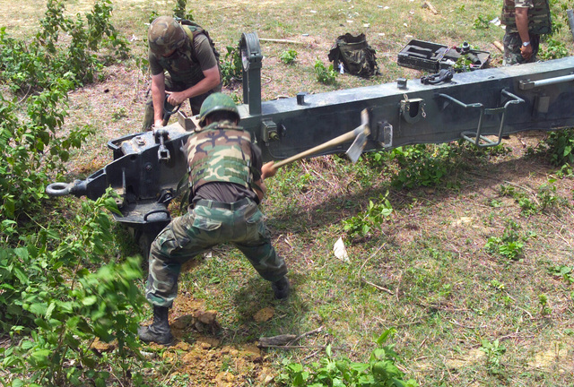 US Marine Corps (USMC) Lance Corporal (LCPL) Landon Simmons (background) S/Battery, 5th Battalion, 10th Marines and a Royal Thai Marine dig an emplacement footing for the M198 155mm Howitzer during a dry fire exercise at Gun Position 10, Pong Nam Ran, Thailand, during Exercise COBRA GOLD 2003