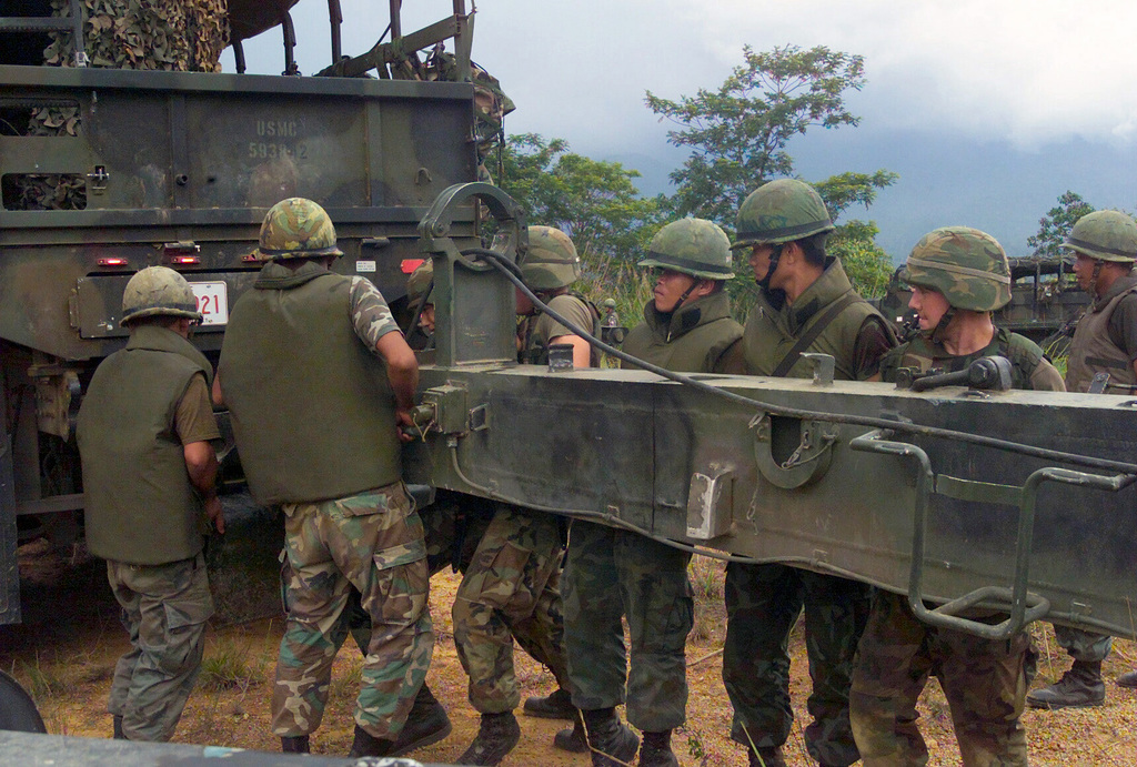US Marine Corps (USMC) Marines assigned to S/Battery, 5th Battalion, 10th Marines, and Royal Thai Marines remove the tow arm from the transport truck, while setting up a M198 155mm Howitzer during a dry fire exercise at Gun Position 10, Pong Nam Ran, Thailand, during Exercise COBRA GOLD 2003