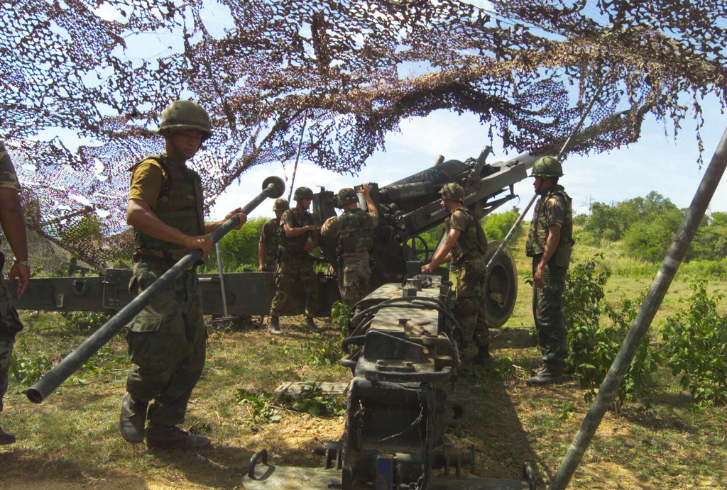 US Marine Corps (USMC) Marines assigned to S/Battery, 5th Battalion, 10th Marines, and Royal Thai Marines practice loading procedures on the M198 155mm Howitzer during a dry fire exercise at Gun Position 10, Pong Nam Ran, Thailand, during Exercise COBRA GOLD 2003