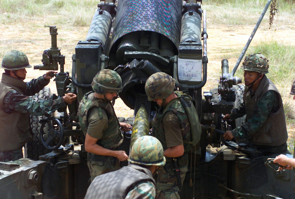 US Marine Corps (USMC) Marines assigned to S/Battery, 5th Battalion, 10th Marines, and Royal Thai Marines load an artillery shell into the M198 155mm Howitzer during a live fire exercise at Gun Position 10, Pong Nam Ran, Thailand, during Exercise COBRA GOLD 2003