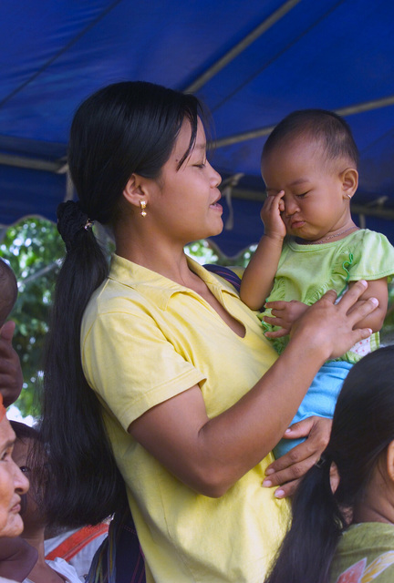 A mother and child are among the local Thai villagers who wait to be examined during the Medical Community Assistance Program (MEDCAP) operated by US Navy Reserve (USNR) personnel, in a village near the Thai border during Exercise COBRA GOLD 2003