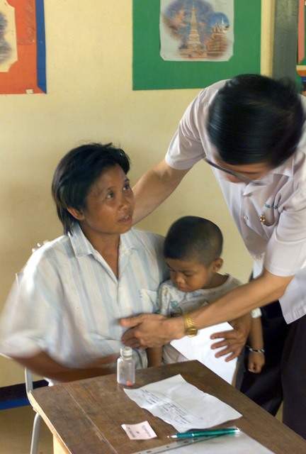 A Thai Doctor gives an examination to a local Thai woman, during the Medical Community Assistance Program (MEDCAP) operated by US Navy Reserve (USNR) personnel, in a village near the Thai border during Exercise COBRA GOLD 2003