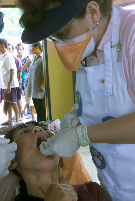 A US Navy (USN) dental assistant from Navy Medical Battalion 17, attends to a Local Thai woman who is having her tooth pulled during the Medical Community Assistance Program (MEDCAP) operated by US Navy Reserve (USNR) personnel, in a village near the Thai border during Exercise COBRA GOLD 2003