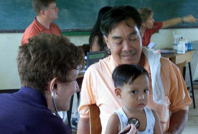 A US Navy (USN) female Doctor examines a young Thai child during the Medical Community Assistance Program (MEDCAP) operated by US Navy Reserve (USNR) personnel, in a village near the Thai border during Exercise COBRA GOLD 2003
