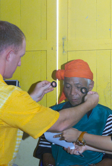 A US Navy (USN) Optical Physician assigned to Navy Medical Hospital San Diego gives an optical examination to a local Thai man, during the Medical Community Assistance Program (MEDCAP) operated by US Navy Reserve (USNR) personnel, in a village near the Thai border during Exercise COBRA GOLD 2003