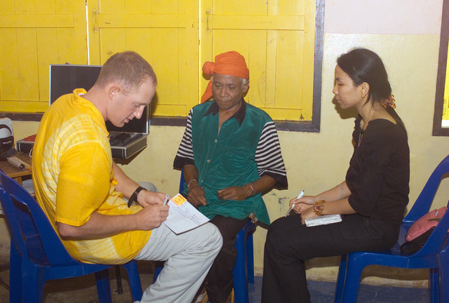 A US Navy (USN) Optical Physician assigned to Navy Medical Hospital San Diego, uses a translator to explain the prescription, after giving an optical examination to a local Thai man, during the Medical Community Assistance Program (MEDCAP) operated by US Navy Reserve (USNR) personnel, in a village near the Thai border during Exercise COBRA GOLD 2003