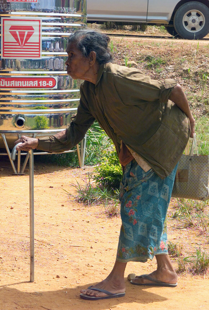 An elderly Thai woman walks with the aid of a walking stick, as she proceeds towards the Medical Community Assistance Program (MEDCAP) operated by US Navy Reserve (USNR) personnel, in a village near the Thai border during Exercise COBRA GOLD 2003