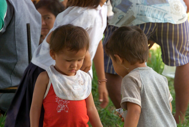 Two small children are among the local Thai villagers who wait to be examined during the Medical Community Assistance Program (MEDCAP) operated by US Navy Reserve (USNR) personnel, in a village near the Thai border during Exercise COBRA GOLD 2003