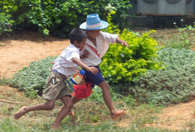 Two Thai boys run and play together after being examined during the Medical Community Assistance Program (MEDCAP) operated by US Navy Reserve (USNR) personnel, in a village near the Thai border during Exercise COBRA GOLD 2003