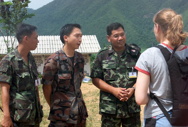 US Army (USA) Private First Class (PFC) Jennifer Gosh (right), interviews three Royal Thai Army soldiers about the free medical attention they are giving along with the US Navy (USN) personnel, during the Medical Community Assistance Program (MEDCAP) in a village near the Thai border during Exercise COBRA GOLD 2003