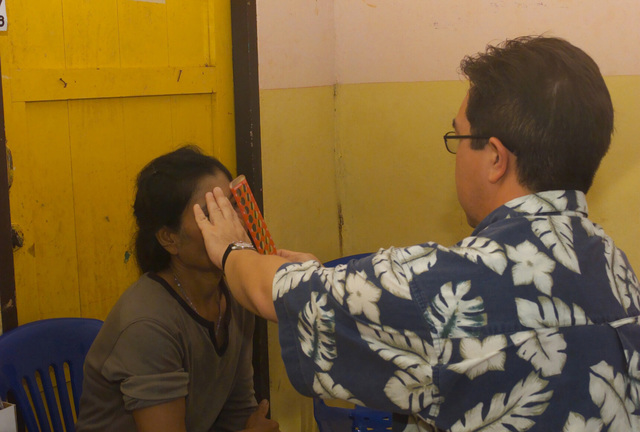 US Navy (USN) Lieutenant Commander (LCDR) Jeff Garcia, assigned to Navy Medical Hospital, San Diego gives an optical examination to a local Thai woman, during the Medical Community Assistance Program (MEDCAP) operated by US Navy Reserve (USNR) personnel, in a village near the Thai border during Exercise COBRA GOLD 2003