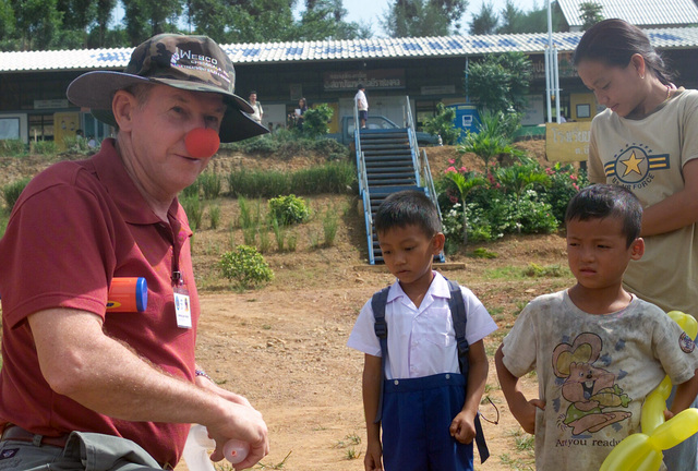 US Navy (USN) Lieutenant Commander (LCDR) Jim Pack, assigned to USN Fleet Hospital Dallas, wears a clowns nose and makes balloon animals for local Thai children, during the Medical Community Assistance Program (MEDCAP) operated by US Navy Reserve (USNR) personnel, in a village near the Thai border during Exercise COBRA GOLD 2003