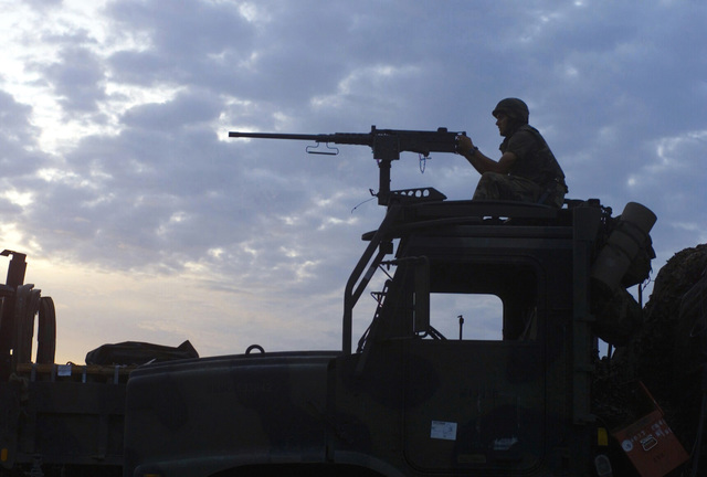 US Marine Corps (USMC) Lance Corporal (LCPL) Zach Campbell, S/Battery, 5th Battalion, 10th Marines, mans a M2HB .50 caliber machine gun mounted atop a cargo truck, while providing security at Gun Position 10, Pong Nam Ran, Thailand, during Exercise COBRA GOLD 2003
