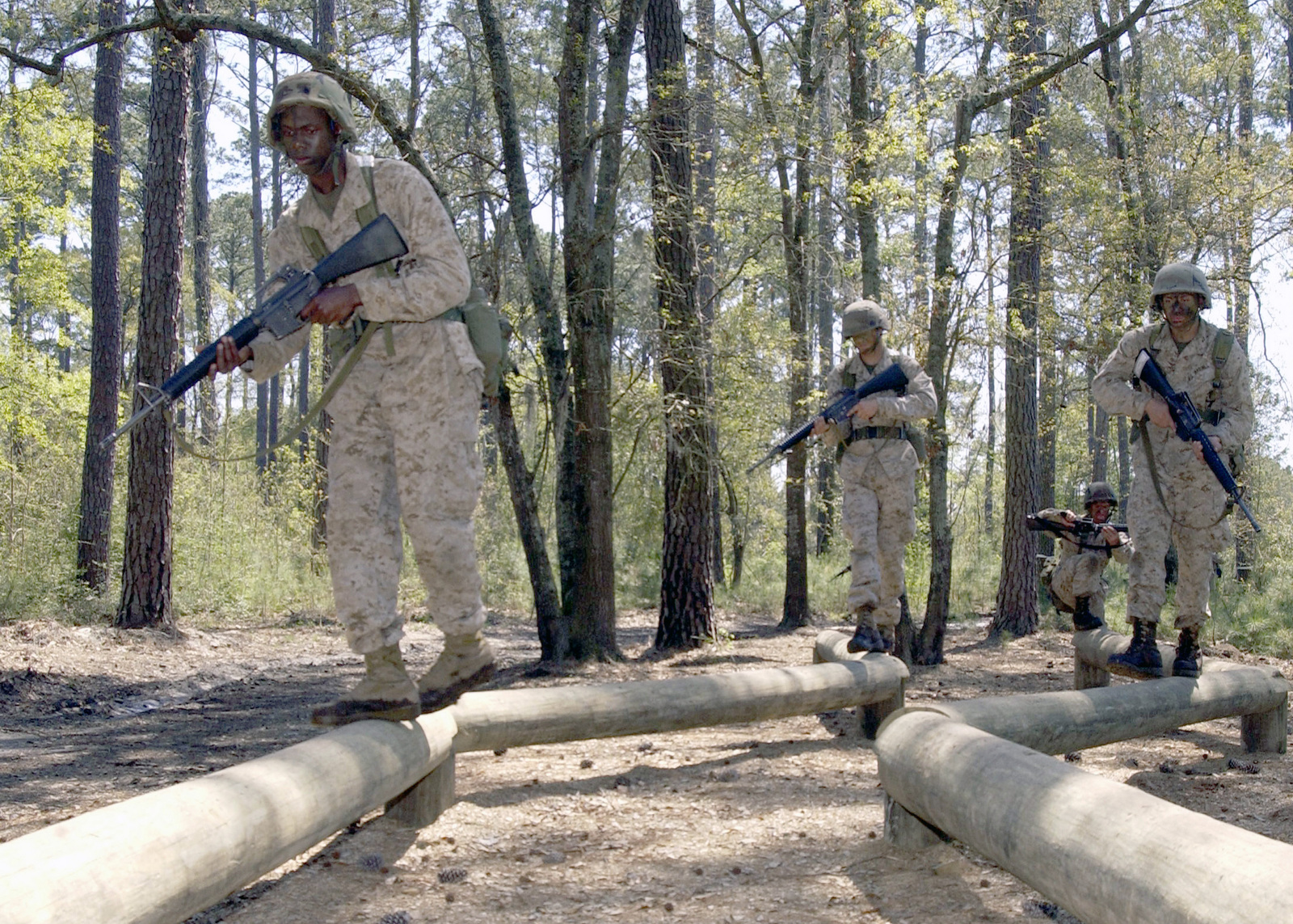 US Marine Corps (USMC) recruits assigned to India Company, Platoon 3024, 3rd Recruit Training Battalion (RTBN), carry their 5.56 mm M16A2 rifles as they navigate an obstacle within the final exercise of recruit training course, at Marine Corps Recruit Depot (MCRD) Parris Island, South Carolina (SC)