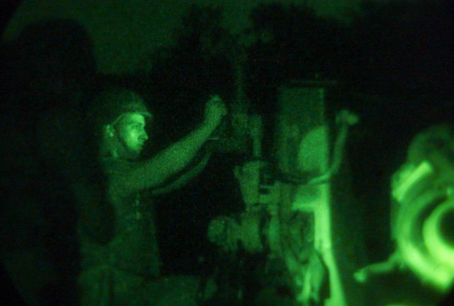 Light enhanced photography showing US Marine Corps (USMC) Lance Corporal (LCPL) Scott Dobson, S/Battery, 5th Battalion, 10th Marines, as he verifies the alignment of the M198 155 Howitzer during a night live fire exercise at Gun Position 10, Pong Nam Ran, Thailand, during Exercise COBRA GOLD 2003