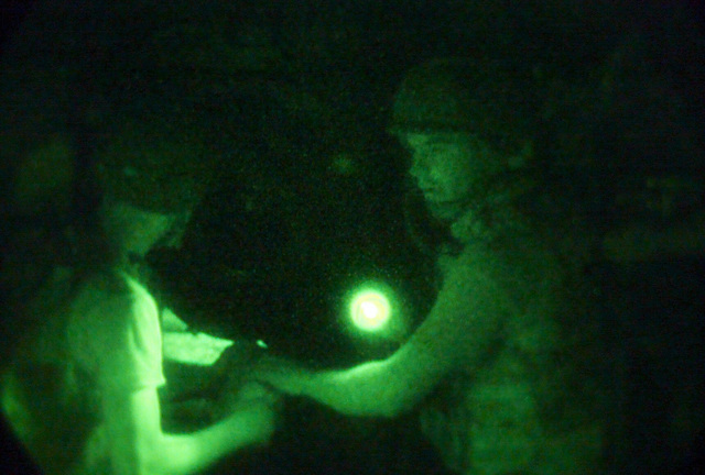 Light enhanced photography showing US Marine Corps (USMC) Lance Corporal (LCPL) Michael Stephens (left) and USMC Corporal (CPL) Phillip Park, S/Battery, 5th Battalion, 10th Marines, as they prepare to fire a M198 155mm Howitzer during a night live fire exercise at Gun Position 10, Pong Nam Ran, Thailand, during Exercise COBRA GOLD 2003