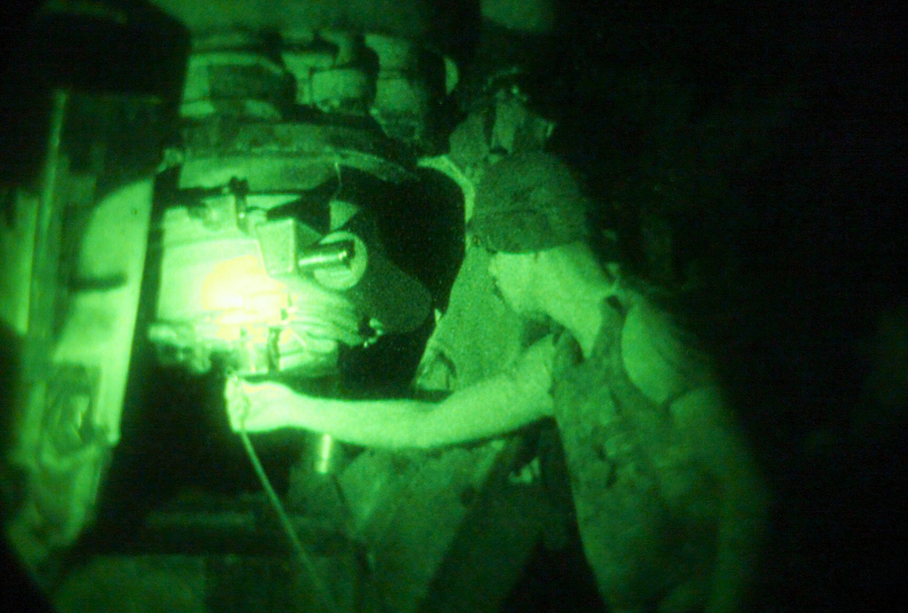Light enhanced photography showing US Marine Corps (USMC) Lance Corporal (LCPL) Michael Stephens, S/Battery, 5th Battalion, 10th Marines, hooks the lanyard to the firing pin of a M198 155mm Howitzer during a night live fire exercise at Gun Position 10, Pong Nam Ran, Thailand, during Exercise COBRA GOLD 2003