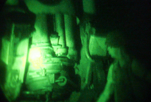 Light enhanced photography showing US Marine Corps (USMC) Lance Corporal (LCPL) Michael Stephens, S/Battery, 5th Battalion, 10th Marines, as he pulls the lanyard of a M198 155mm Howitzer during a night live fire exercise at Gun Position 10, Pong Nam Ran, Thailand, during Exercise COBRA GOLD 2003