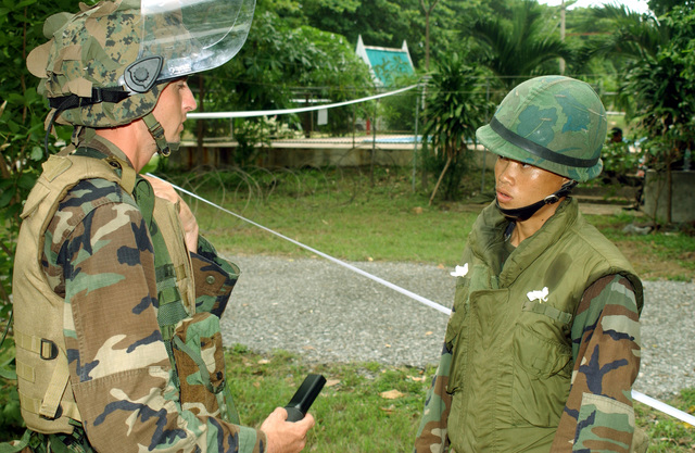 US Marine Corps (USMC) Corporal (CPL) Mathew Solmmes, left and Royal Thai Marine CHIEF PETTY Officer First Class (PO1) Wattanapan Chantarasaen, consult on tactics in order to protect Evacuees during a Non-Combatant Evacuation Operation (NEO), part of Exercise COBRA GOLD 2003. Corporal (CPL) Mathew Solmmes, is attached to the 1ST Battalion, 3rd Marines, from Kaneohe Bay, Hawaii