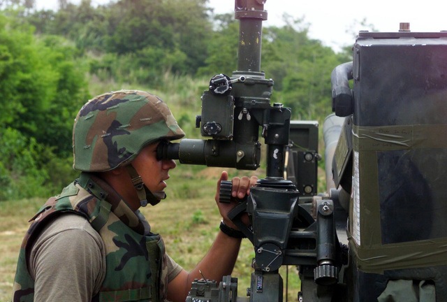 US Marine Corps (USMC) Corporal (CPL) Peter Ospina, S/Battery, 5th Battalion, 10th Marines, verifies the alignment of the M198 155mm Howitzer, during a live fire exercise at Gun Position 10, Pong Nam Ran, Thailand, during Exercise COBRA GOLD 2003
