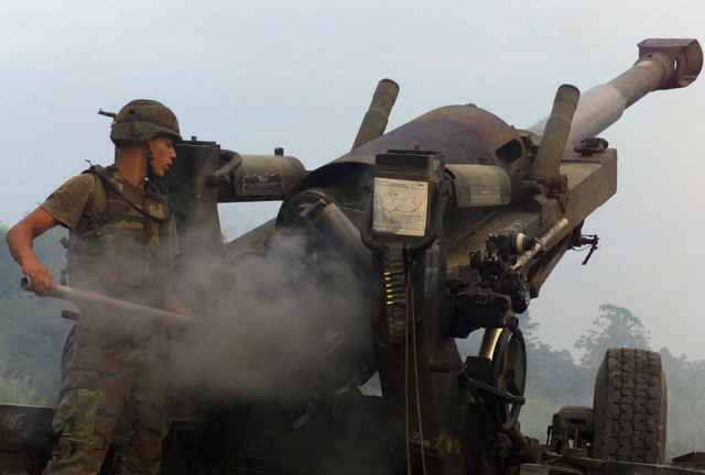 US Marine Corps (USMC) Lance Corporal (LCPL) Michael Stephens, S/Battery, 5th Battalion, 10th Marines, clears the smoke from the bore of a M198 155mm Howitzer, during a live fire exercise at Gun Position 10, Pong Nam Ran, Thailand, during Exercise COBRA GOLD 2003